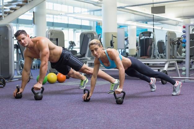 Bodybuilding homem e mulher levantando kettlebells na posição de prancha