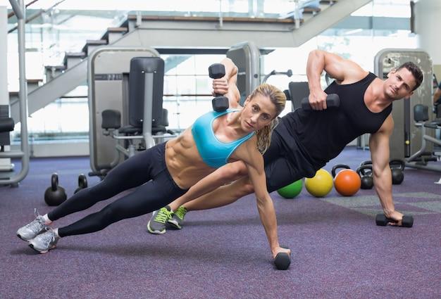 Bodybuilding homem e mulher segurando dumbbells na posição de prancha