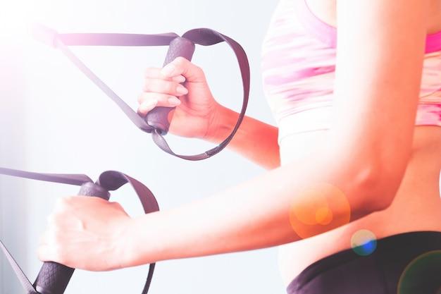 Bodybuilding. mulher forte que se exercita com correia trx.