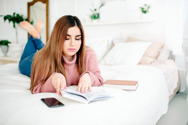 Bodypositive jovem lê um livro enquanto estava deitado em uma cama em casa, telefone fica nas proximidades, um quarto confortável e brilhante