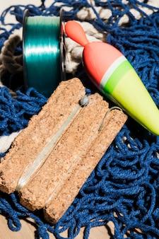 Bóia de pesca e linha de pesca na placa de cortiça sobre a rede de pesca azul