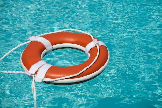 Bóia de salvamento de equipamentos de segurança ou bóia de resgate flutuando no mar para resgate de ajuda no conceito de água