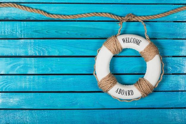 Boia salva-vidas em fundo azul de madeira com lugar para texto