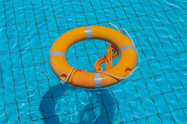 Boia salva-vidas flutuando sobre a água azul ensolarada da piscina