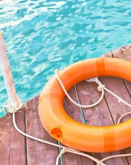 Boia salva-vidas laranja com corda em um cais de madeira perto do mar.