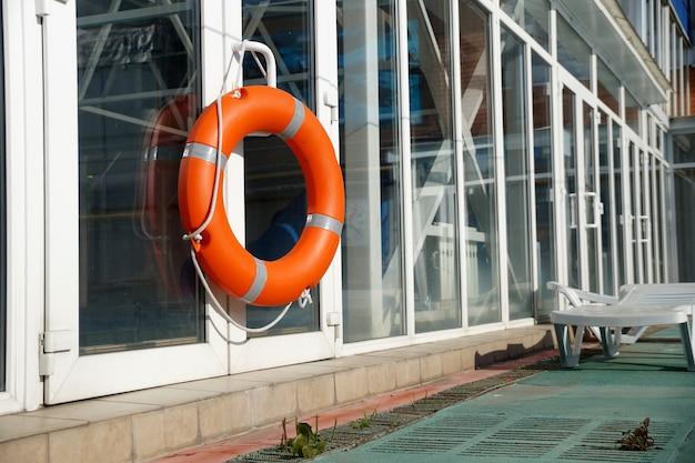 Bóia salva-vidas laranja na parede de proteção da piscina