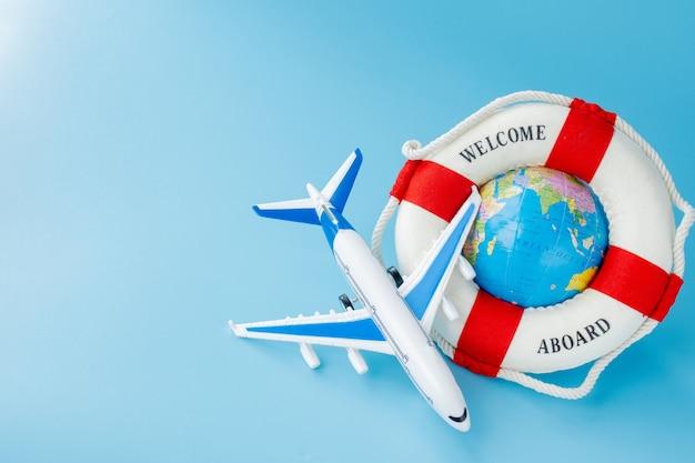 Boia salva-vidas, modelo de avião e globo. conceito de verão ou férias. copie o espaço.