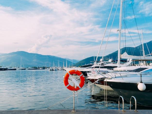 Boia salva-vidas na marina para iates. círculo vermelho na doca do barco. porto montenegro, montenegro.