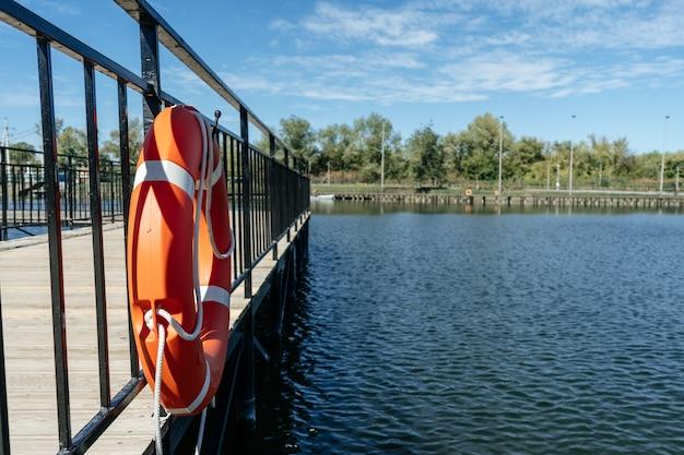 Boia salva-vidas pendurada em um píer com vista para o rio