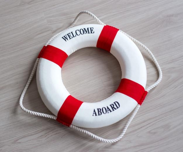 Boia salva-vidas vermelha com texto de boas-vindas a bordo sobre fundo de madeira