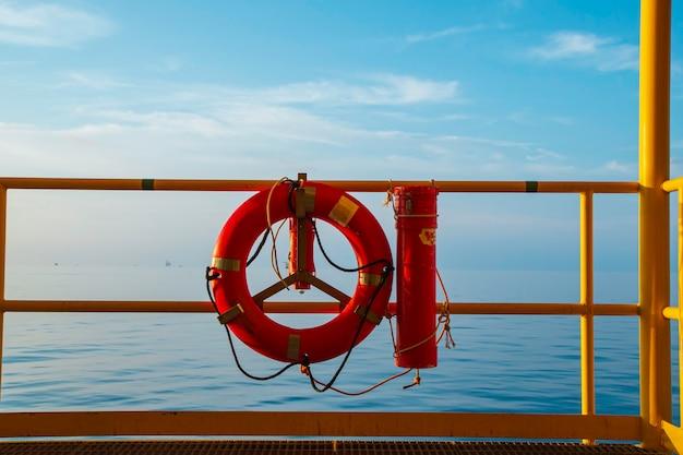 Boia salva-vidas vermelha em uma plataforma no mar.