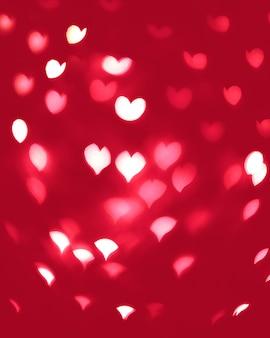 Bokeh abstrato desfocado de coração em tons de vermelho e rosa