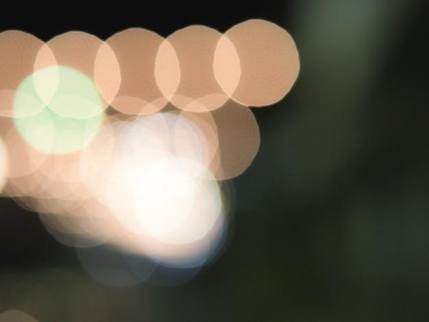 Bokeh alaranjado abstrato da luz do círculo no fundo escuro.