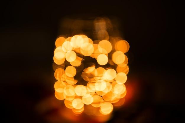 Bokeh amarelo de luz. bokeh dourado de luz. luz desfocado com fundo preto.