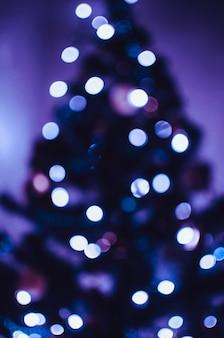 Bokeh azul de uma guirlanda de led em uma árvore de natal. conceito de bokeh e luz festivos. copie o espaço.