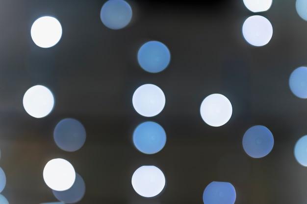 Bokeh brilhante branco e azul em pano de fundo escuro