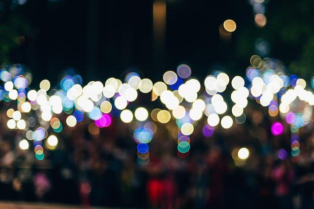 Bokeh colorido turva redondo das luzes no fundo escuro