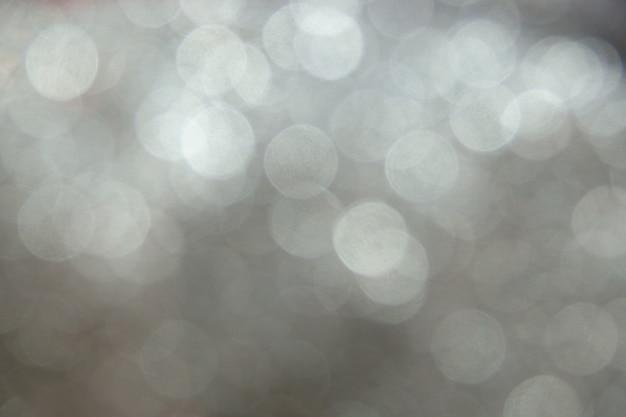 Bokeh de brilho de prata das luzes de natal. fundo desfocado