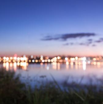 Bokeh de luz da cidade com vista para o lago, fundo borrado na natureza