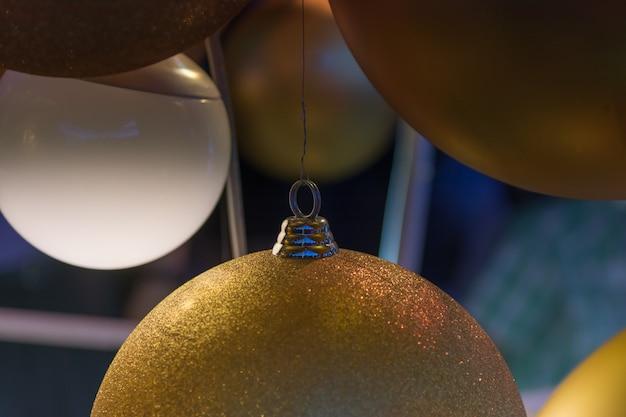 Bokeh dourado abstrato da bola e da noite do natal, luz da cidade para o fundo.