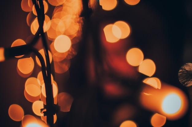 Bokeh laranja quente da guirlanda de led na fachada do edifício. conceito de bokeh e luz festivos de natal. modelo de design. copie o espaço.