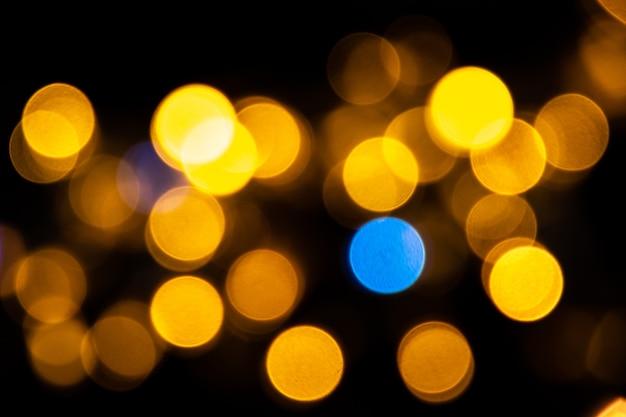 Bokeh perfeito ilumina o fundo. círculos de luz amarelos e azuis abstratos desfocados.
