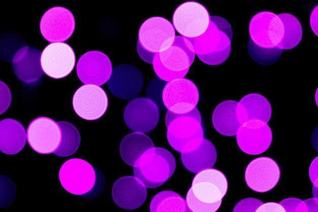 Bokeh roxo abstrato desfocado em fundo preto. desfocado e borrado muitas luzes redondas.