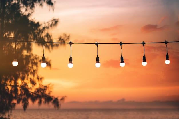 Bokeh turva luz no pôr do sol com decoração de luzes da corda amarela no restaurante de praia