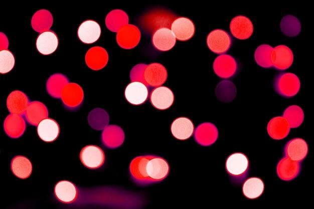 Bokeh vermelho abstrato desfocado em fundo preto. desfocado e borrado muitas luzes redondas.