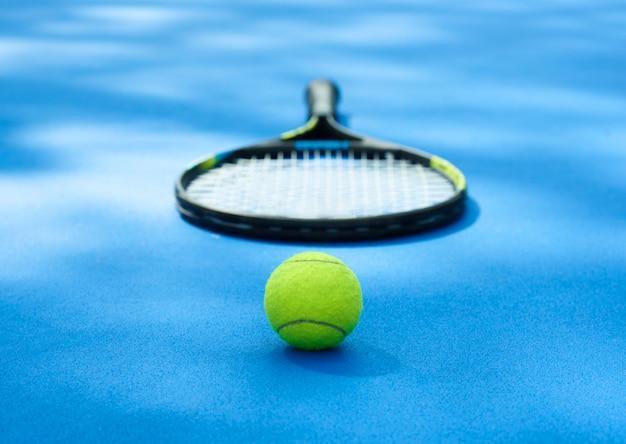 Bola amarela está deitada no tapete de quadra de tênis azul com raquete profissional.