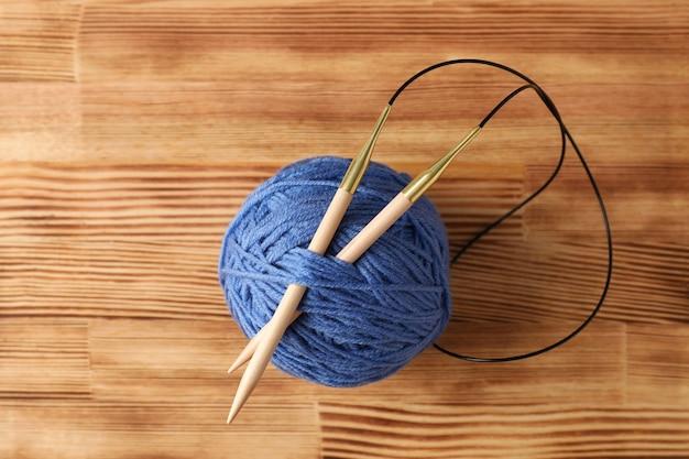 Bola azul de lã com agulhas de tricô em uma mesa de madeira clara.