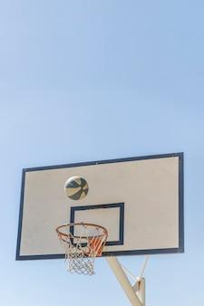 Bola caindo na cesta de basquete contra o céu claro