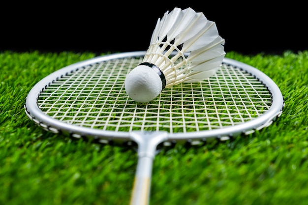 Bola de badminton e raquete na grama em fundo preto