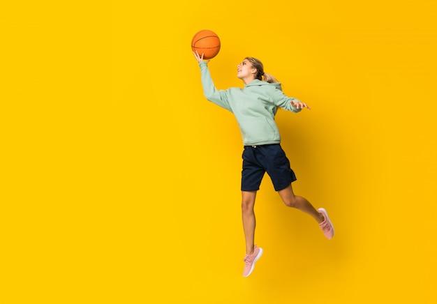 Bola de basquete de garota adolescente pulando