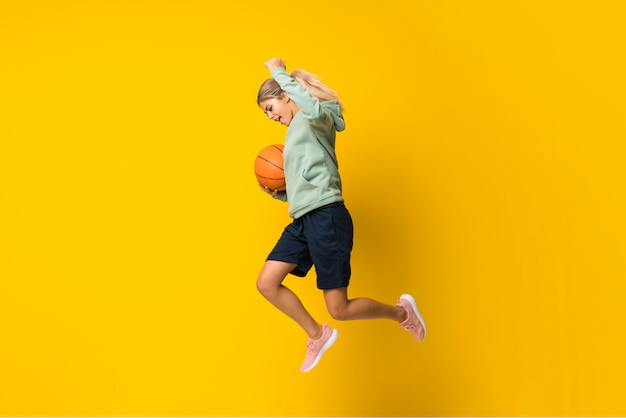 Bola de basquete garota adolescente pulando isolado parede amarela