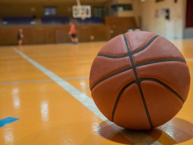Bola de basquete na quadra com linha de lance livre, jogadores fora de foco