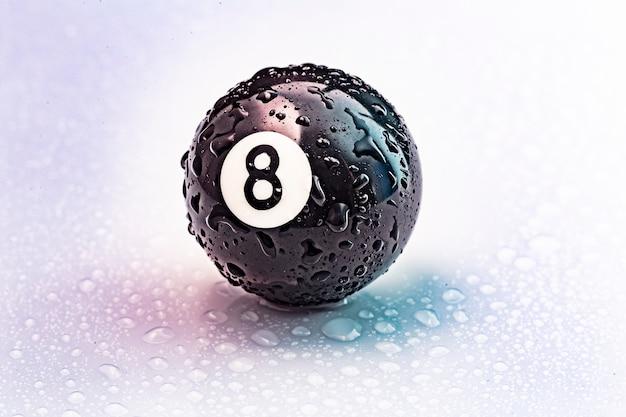 Bola de bilhar número oito com gotas de água em branco