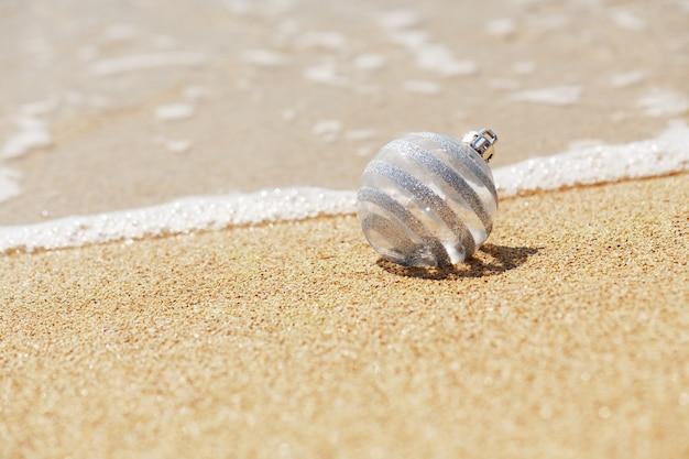 Bola de brilho branco de natal na praia tropical perto do oceano, um feriado de natal e inverno