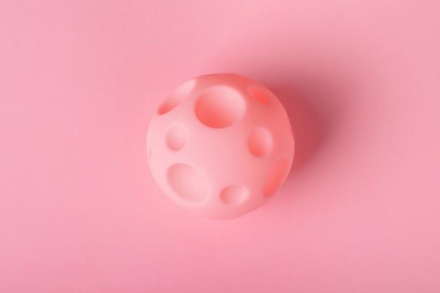 Bola de brinquedo com crateras em um fundo brilhante, o conceito de conquista do espaço e novos planetas