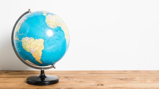 Bola de carrinho mapa global na mesa de madeira
