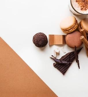 Bola de chocolate; macaroons e copo de café com ingredientes em pano de fundo branco