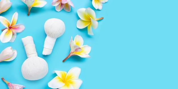Bola de compressa de ervas para massagem tailandesa e tratamento de spa com flor de plumeria ou frangipani sobre fundo azul. copie o espaço