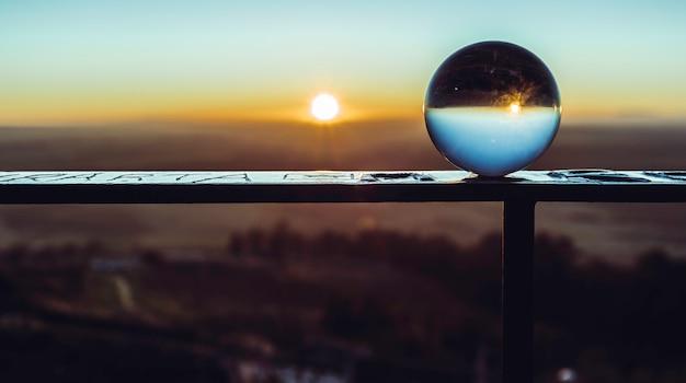 Bola de cristal no corrimão refletindo o céu e o sol do amanhecer