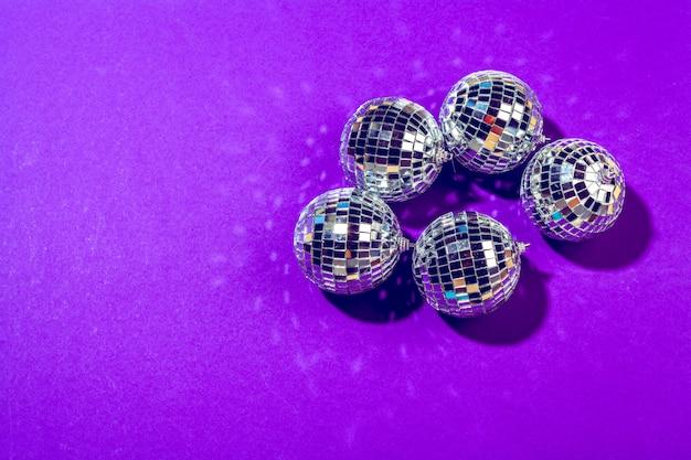 Bola de discoteca brilha no fundo roxo close-up