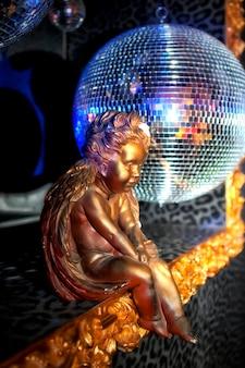 Bola de discoteca com raios brilhantes e escultura de bronze de menino com asas ou um anjo sentado na frente da bola, foto de fundo de festa à noite. show de luzes. espaço de direitos autorais. grande espaço para inscrição ou logotipo