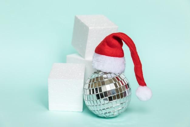 Bola de discoteca de composição simplesmente mínima no chapéu de papai noel e formas geométricas do pódio das formas do cubo