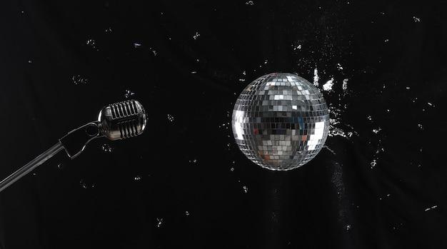 Bola de discoteca e microfone em fundo preto