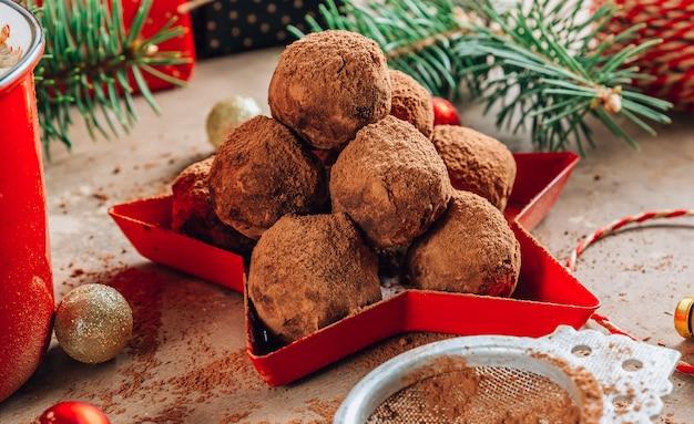 Bola de doces caseiros de trufas de chocolate em um fundo de natal. foco seletivo