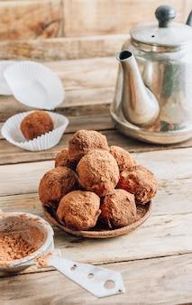 Bola de doces de trufas de chocolate caseiras em um prato polvilhado com cacau em um fundo de madeira enferrujado. top vew. foto vertical