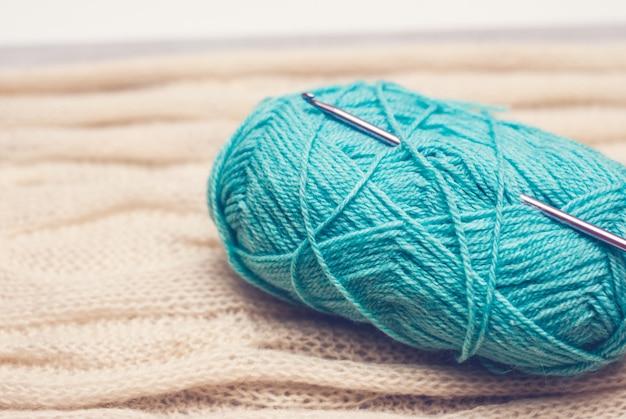 Bola de fio azul com agulha de crochet